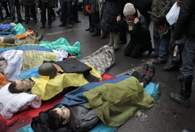 Activists pay respects to protesters killed in clashes with police, in Kiev's Independence Square, the epicenter of the country's current unrest, Thursday, February 20, 2014. (Photo by Sergei Chuzavkov/AP Photo)