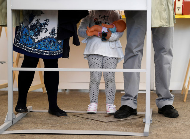 A girl and her parents are seen in one of the booths before voting during Spain's general election in Pola de Siero, April 28, 2019. (Photo by Eloy Alonso/Reuters)