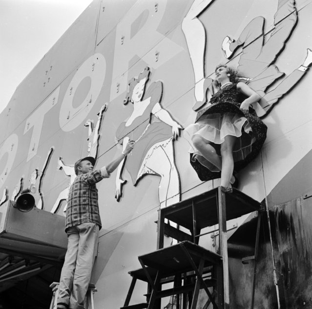 Herman Huseby, art director at the Rockaway Playland Amusement Park in Belle Harbour, New York, works on a mural with the help of a model, circa 1950. (Photo by Orlando/Three Lions/Getty Images)