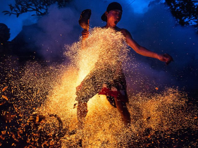 "A Balinese man kicks up the fire during the ""Mesabatan Api"" ritual ahead of Nyepi Day on March 20, 2015 in Gianyar, Bali, Indonesia. Mesabatan Api is held annually a day before the Nyepi Day of Silence, as it symbolizes the purification of universe and human body through fire. Nyepi is a Hindu celebration observed every New Year according to the Balinese calendar. (Photo by Agung Parameswara/Getty Images)"