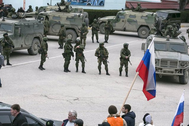 Pro-Russian men hold Russian flags in front of armed servicemen near Russian army vehicles outside a Ukrainian border guard post in the Crimean town of Balaclava March 1, 2014. Ukraine accused Russia on Saturday of sending thousands of extra troops to Crimea and placed its military in the area on high alert as the Black Sea peninsula appeared to slip beyond Kiev's control. (Photo by Baz Ratner/Reuters)
