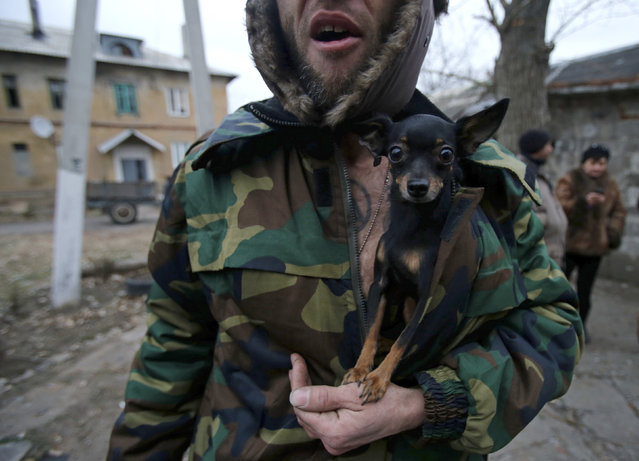 A man holds a dog in front of a damaged building by shelling in the western part of Donetsk, eastern Ukraine, November 27, 2014. (Photo by Antonio Bronic/Reuters)