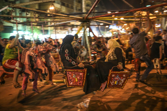 In this Tuesday, May 12, 2015 photo, families ride a swing as Muslims take part in a religious festival, or moulid, which commemorates the birth of the Muslim Prophet Muhammad's granddaughter, Sayyeda Zeinab, outside the mosque and shrine named for her, in Cairo, Egypt. (Photo by Mosa'ab Elshamy/AP Photo)