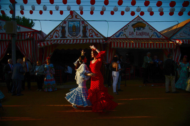 "Women in traditional Sevillian dresses dance during the ""Feria de Abril"" (April Fair) festival in Seville on May 6, 2019. The fair dates back to 1847 when it was originally organized as a livestock fair but has turned into a week of flamenco dancing, music and bullfighting. (Photo by Cristina Quicler/AFP Photo)"