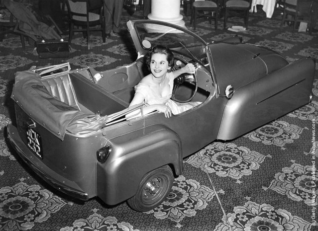 1955: Model Gay McGregor shows off the latest 1956 model Bond Minicar three-wheeler, at its London preview