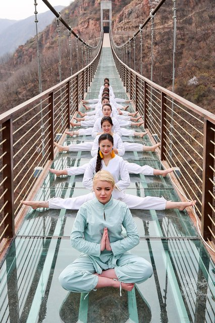 Yoga enthusiasts pose on the glass suspension bridge at Fuxishan Tourism Resort, March 30, 2016, in Zhengzhou, China. People did yoga on the glass suspension bridge which was about 100 meter high from the valley bottom in Zhengzhou. (Photo by VCG via Getty Images)