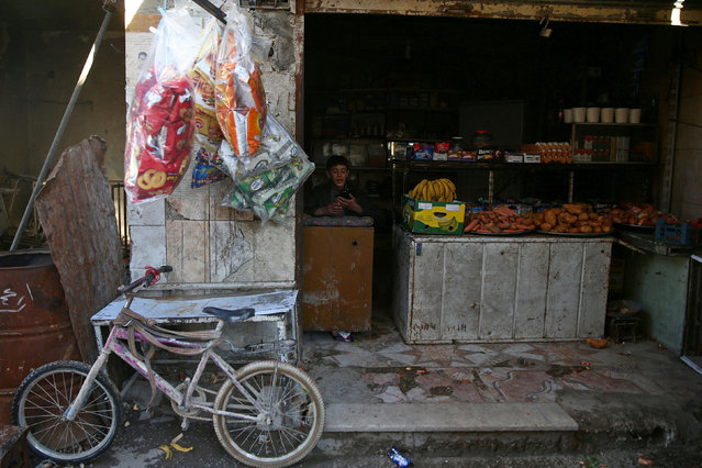 A youth sits inside a shop in the rebel-held besieged Douma neighbourhood of Damascus, Syria February 15, 2017. (Photo by Bassam Khabieh/Reuters)