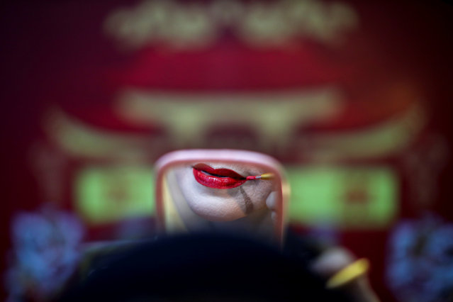 A member of a Chinese opera troupe applies make-up before performing at a shrine in Bangkok, Thailand, on May 13, 2019. (Photo by Athit Perawongmetha/Reuters)