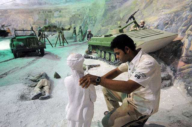 An Afghan laborer works on a plaster statue depicting the victims of the Soviet invasion of Afghanistan, part of a display at The Jihad Museum in Herat, on August 8, 2009. (Photo by Shah Marai/AFP Photo via The Atlantic)