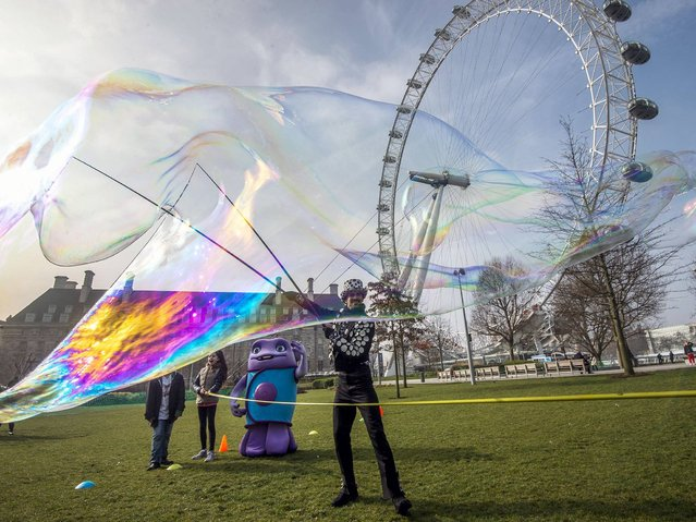"""Beside the landmark, """"London Eye"""", Bubbleologist, Sam Heath, otherwise know as Samsam Bubbleman, attempts to break his tenth Guinness World Record by creating a 23 cubic metres bubble in central London on March 18, 2015. (Photo by Niklas Halle'n/AFP Photo)"""