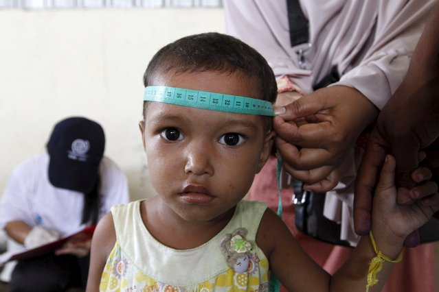 A Rohingya child, who recently arrived in Indonesia by boat, is measured and weighed at a shelter in Kuala Langsa, in Indonesia's Aceh Province, May 17, 2015.  The United Nations has called on countries around the Andaman Sea not to push back the thousands of desperate Bangladeshis and Rohingya Muslims from Myanmar now stranded in rickety boats, and to rescue them instead. (Photo by Roni Bintang/Reuters)