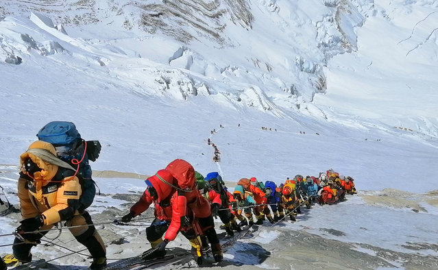 In this May 22, 2019 photo, a long queue of mountain climbers line a path on Mount Everest just below camp four, in Nepal. Seasoned mountaineers say the Nepal government's failure to limit the number of climbers on Mount Everest has resulted in dangerous overcrowding and a greater number of deaths. (Photo by Rizza Alee/AP Photo)