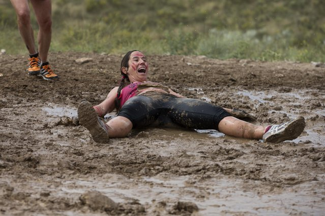 A participant lies in the mud as she takes part in the Mud Day athletic event in Toledo, Spain, Saturday, May 23, 2015. (Photo by Paul White/AP Photo)