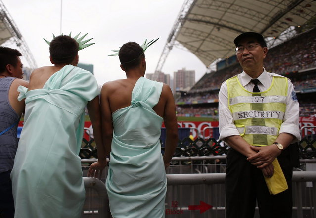 A security guard stands beside rugby fans on the last day of the three-day Hong Kong Sevens rugby tournament, as part of the Sevens World Series, in Hong Kong March 30, 2014. (Photo by Bobby Yip/Reuters)