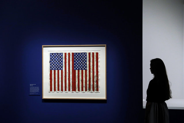 "A British Museum representative poses for photographs next to ""Flag I"" by Jasper Johns which features in ""The American Dream: pop to the present"" exhibition during a media photocall at the British Museum in London, Monday, March 6, 2017. (Photo by Matt Dunham/AP Photo)"