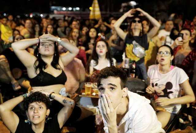 Brazilian fans of women's soccer react as they watch the soccer match between France and Brazil on a TV screen at a bar in Sao Paulo, Brazil, June 23, 2019. (Photo by Nacho Doce/Reuters)