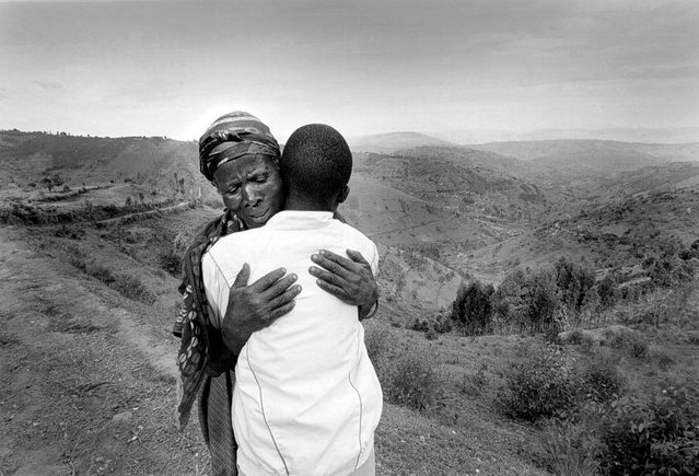 Jean Baptiste Maniraguha, 15, is hugged by his grandmother, Pascasie Myiramiruho. His parents died during the war. The Red Cross transported him back to his commune after his arrival from Zaire when he was taken to Gisimbe orphanage while his family was traced; 1996. (Photo by Carol Guzy/The Washington Post)