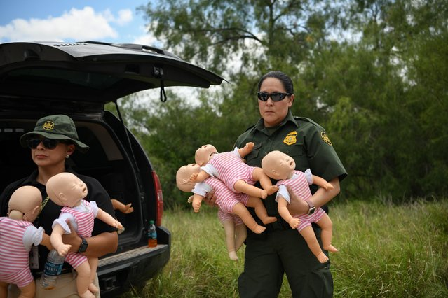 "A U.S. Border Patrol agent holds infant dolls in preparation for a demonstration during a ""Border Safety Initiative"" media event at the U.S.-Mexico border in Mission, Texas, U.S., July 1, 2019. (Photo by Loren Elliott/Reuters)"
