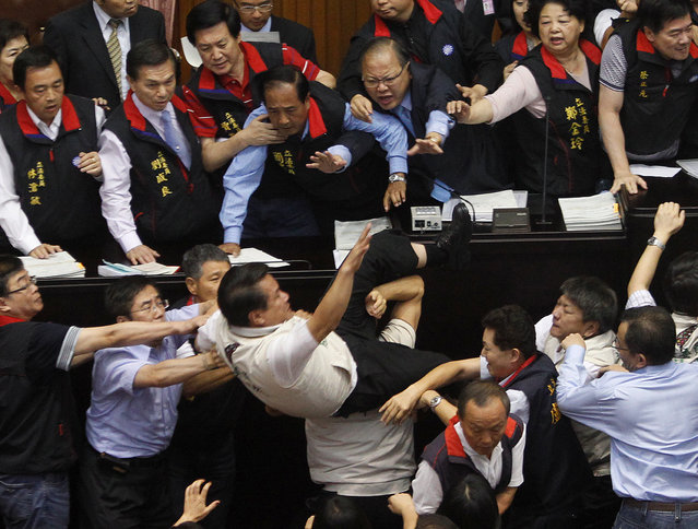 Opposition Democratic Progressive Party (DPP) legislator Kuo Wen-chen falls off the podium while scuffling with ruling Nationalist Party (KMT) legislators at the Legislative Yuan in Taipei July 8, 2010. (Photo by Nicky Loh/Reuters)