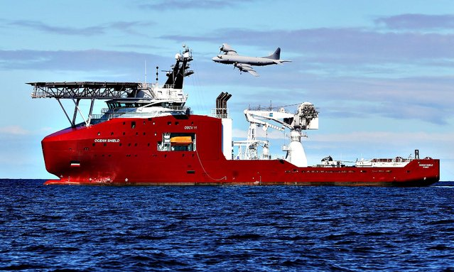 In this April 9, 2014 photo provided by the Australian Defense Force, a Royal Australian Air Force AP-3C Orion flies past Australian Defense vessel Ocean Shield on a mission to drop sonar buoys to assist in the acoustic search of the missing Malaysia Airlines Flight 370 in the southern Indian Ocean. (Photo by LSIS Bradley Darvill/AP Photo/Australian Defense Force)