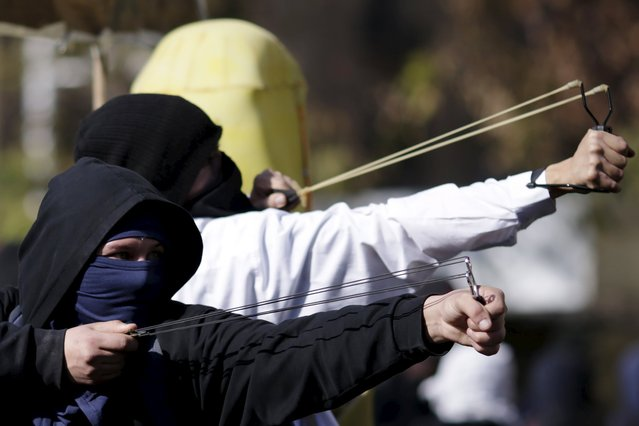 Protesters use slingshots against police during a demonstration to demand changes in the Chilean education system in Santiago, Chile June 25, 2015. (Photo by Ueslei Marcelino/Reuters)