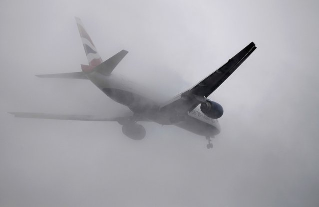 A British Airways passenger aircraft flies through low cloud as it prepares to land at Heathrow airport in west London, Britain, January 7, 2017. (Photo by Toby Melville/Reuters)