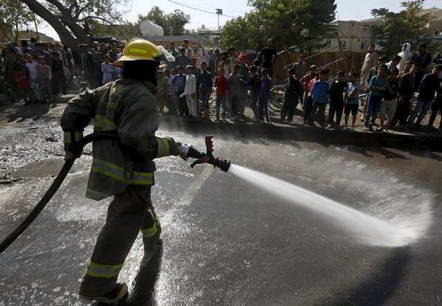 A fire fighter sprays water to clean the site of a suicide car bomb attack in Kabul, Afghanistan, June 30, 2015. (Photo by Omar Sobhani/Reuters)