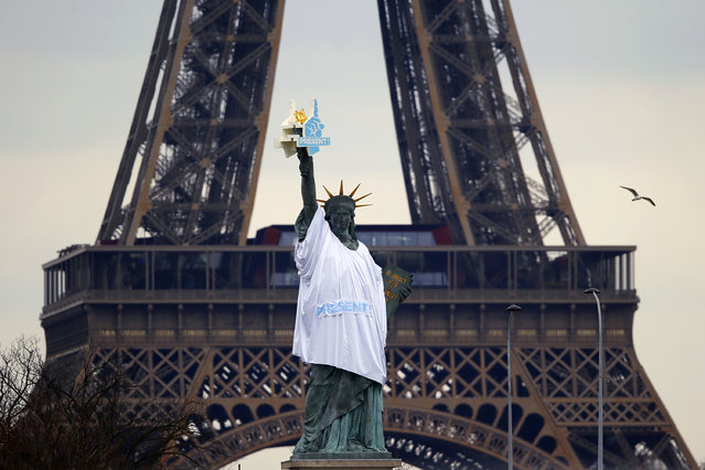 """A replica of the Statue of Liberty is decorated with a t-shirt reading """"Present"""" in Paris, Thursday, March 23, 2017. French environmentalist Nicolas Hulot and Emmaus France director Thierry Kuhn launched an appeal called 'Present' to launch a solidarity movement with some 80 NGOs and associations just one month before the first round of the presidential election and to push the Presidential candidates for more solidarity in their campaign program. (Photo by Francois Mori/AP Photo)"""