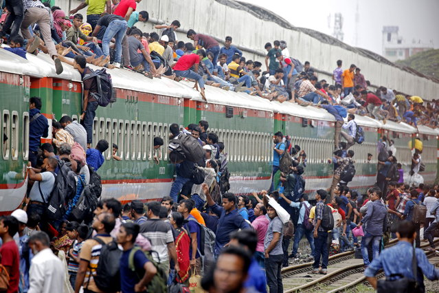 Bangladeshi people climb on the roof of an overcrowded train as they travel to their home villages to celebrate Eid-al-Adha, at the Kamlapur Railway Station in Dhaka, Bangladesh, 09 August 2019. Eid al-Adha is the holiest of the two Muslims holidays celebrated each year, it marks the yearly Muslim pilgrimage (Hajj) to visit Mecca, the holiest place in Islam. Muslims slaughter a sacrificial animal and split the meat into three parts, one for the family, one for friends and relatives, and one for the poor and needy. (Photo by Monirul Alam/EPA/EFE)
