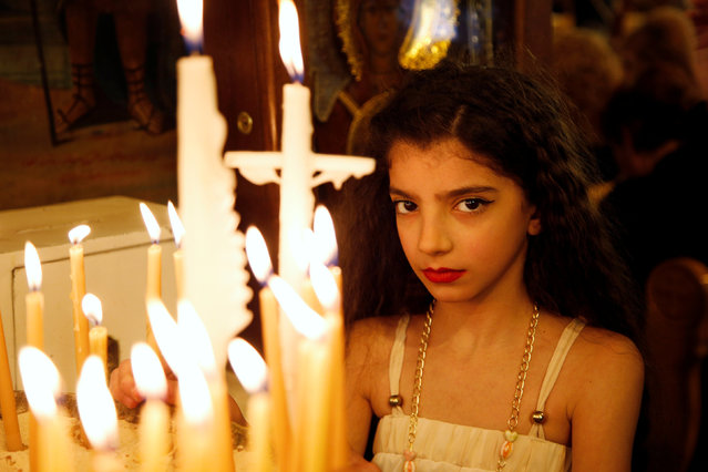 A girl stands near candles inside Al-Saleeb church during Palm Sunday in al-Qassaa, Damascus, Syria April 9, 2017. (Photo by Omar Sanadiki/Reuters)