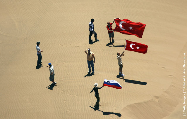Fans stand on a sand dune waiting for the competitors during stage seven of the 2012 Dakar Rally