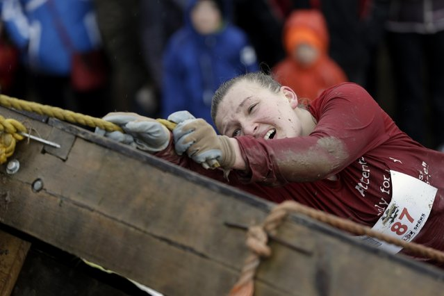 A woman reacts as she competes during the Strong Race competition near Tukums May 4, 2014. (Photo by Ints Kalnins/Reuters)