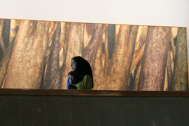 An Iranian women walks past a painting in Tehran's Museum of Contemporary Art, Iran May 3, 2016. (Photo by Marius Bosch/Reuters)