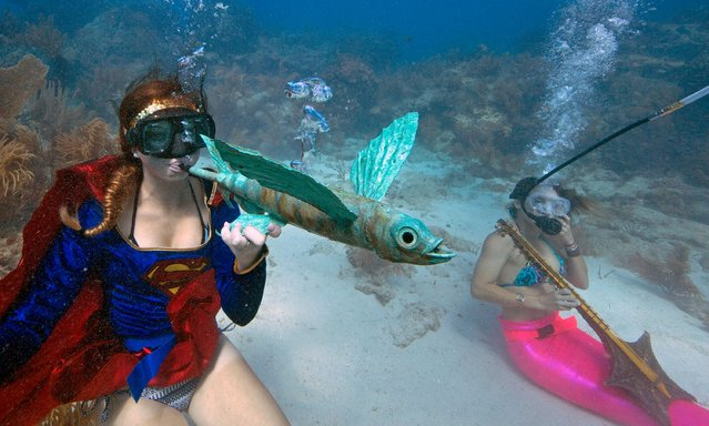 Kaitlin Goddard, left, costumed as superhero, blows through an artist's flying fish whistle during the Underwater Music Festival in the Florida Keys National Marine Sanctuary off Big Pine Key, Florida in this July 11, 2015 handout photo. (Photo by Rob Care/Reuters/Florida Keys News Bureau)