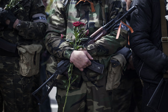 A pro-Russian gun man holds his machine gun and a flower during the commemoration of Victory Day in Donetsk, Ukraine, Friday, May 9, 2014. Victory Day honors the armed forces and the millions who died in World War II. This year it comes as Russia is locked in the worst crisis with the West, over Ukraine, since the end of the Cold War. (Photo by Manu Brabo/AP Photo)