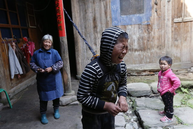 Xie Guobiao (C), 11, tied to a pillar with a rope, cries as his grandmother (L) and younger sister look on at his home in Daohui village of Lishui, Zhejiang province May 7, 2014. (Photo by William Hong/Reuters)