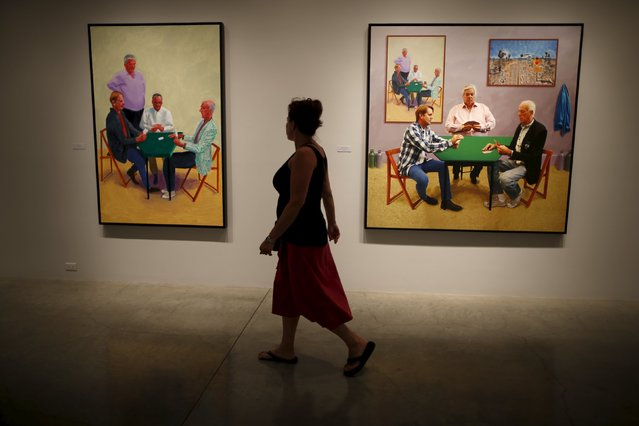 """A woman walks past photographic drawing """"A Bigger Card Players"""" (R) and painting """"Card Players #3"""" by British artist David Hockney at a preview of Hockney's exhibition """"Painting and Photography"""" at the L.A. Louver gallery in Venice, Los Angeles, California, United States July 15, 2015. (Photo by Lucy Nicholson/Reuters)"""