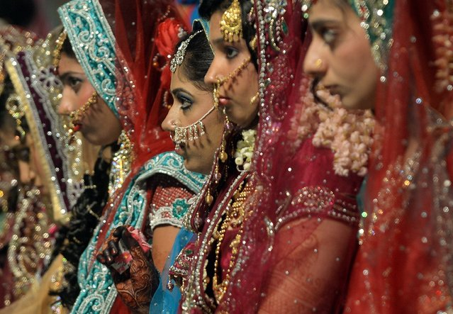 Indian Muslim brides take part in a mass marriage ceremony in Mumbai on May 11, 2014. Mass marriages generally organised by social organisations to cut ceremony costs are common in India with its billion plus population where the custom of dowry and expensive gifts from the bride's family still pravails among certain segments of society. (Photo by Punit Paranjpe/AFP Photo)