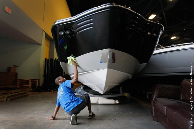 Workers prepare boats for tomorrow's opening day of the four day long Progressive Insurance Miami International Boat Show at the Miami Beach Convention Center