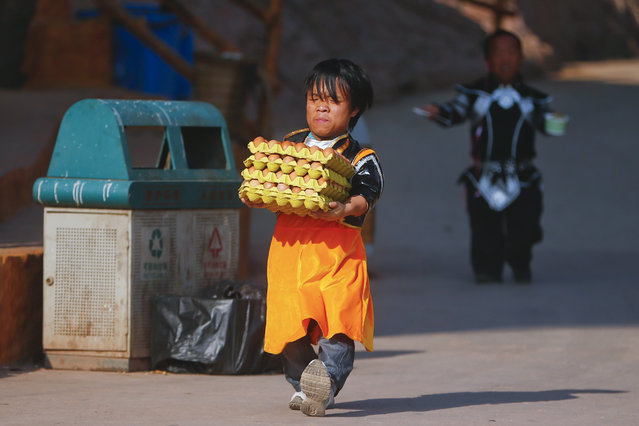 """Staff member of """"Dwarf Empire"""" Luo Gang (L) carries eggs to one of the shops inside the Dwarf Empire theme park before the start of the day outside Kunming, China's Yunnan province, 04 April 2013. (Photo by Diego Azubel/EPA)"""
