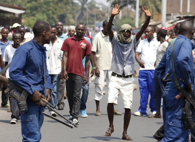 Protestors jeer police as they march through rock strewn streets in Bujumbura's Niyakabiga district on presidential election day in Burundi, July 21, 2015. A policeman and an opposition official died in violence marring the start of Burundi's presidential election, already hit by opposition boycotts and protests over President Pierre Nkurunziza's decision to run for a third term. (Photo by Mike Hutchings/Reuters)