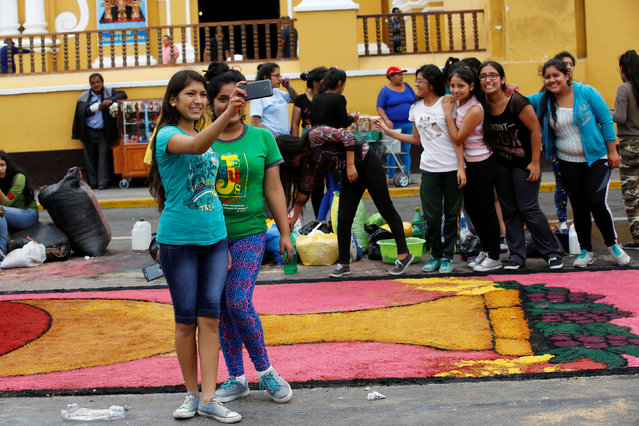 People take selfie a with sawdust and floral carpet during the feast of Corpus Christi in downtown Trujillo, Peru, May 26, 2016. (Photo by Mariana Bazo/Reuters)
