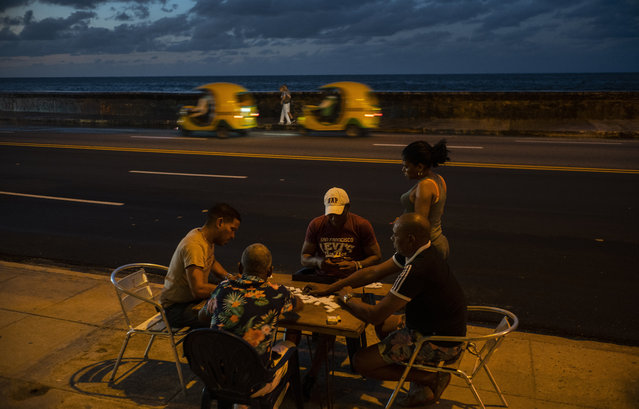 In this November 10, 2019 photo, people play dominoes near the malecon sea wall at sunset in Havana, Cuba. (Photo by Ramon Espinosa/AP Photo)