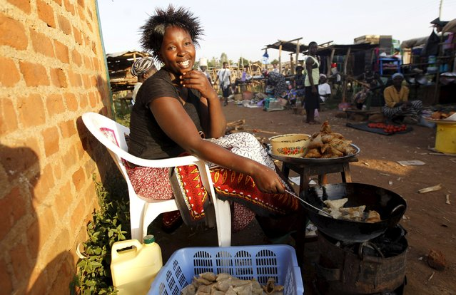 "Vivian Odhiambo, 24, frys samosas in the trading centre of Kogelo, west of Kenya's capital Nairobi, July 14, 2015. Odhiambo said, ""Obama is our hero and we wait to welcome him back home again. We in Kogelo have witnessed general growth and we are proud of being associated with the Obamas"", she added. (Photo by Thomas Mukoya/Reuters)"