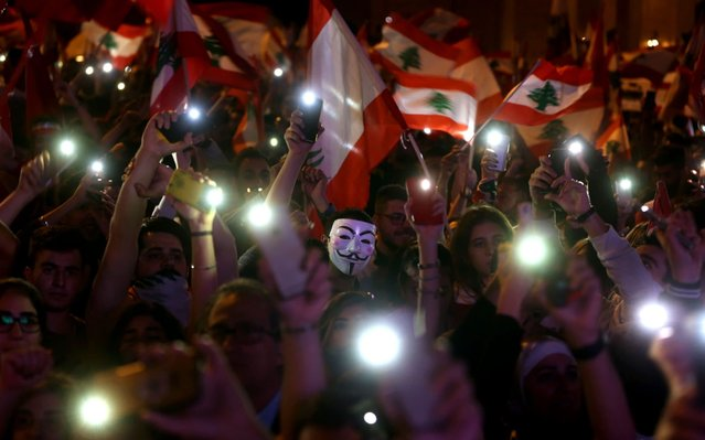 "Lebanese demonstrators take part in a civilian Independence Day parade in Beirut's Martyr Square on November 22, 2019, more than a month into protests demanding an overhaul of the entire political system. Lebanese celebrated 76 years of national self-rule Friday, tens of thousands massing for joyous street festivities rather than stiff military parades to hail what a new protest movement calls ""real independence"". (Photo by Patrick Baz/AFP Photo)"