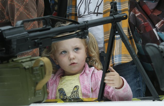 A girl examines a machine gun at a weapon exhibition, during celebrations for Navy Day in St.Petersburg, Russia, Sunday, July 26, 2015. The celebration of Navy Day in Russia is traditionally marked on the last Sunday of July. (Photo by Dmitry Lovetsky/AP Photo)