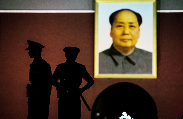 Chinese Paramilitary security force officers stand under a portrait of Mao Zedong outside the Forbidden City, at Tiananmen Square in Beijing, on June 2, 2014. (Photo by Kevin Frayer/Getty Images)