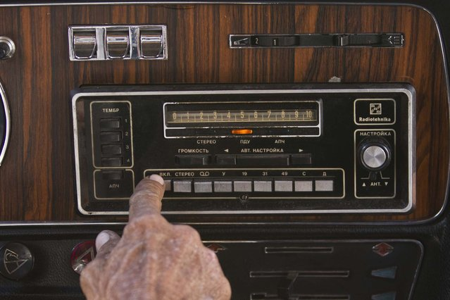 "In this June 18, 2014 photo, taxi driver Moises Suarez turns on the radio inside the Soviet-made limousine taxi cab that once belonged to Fidel Castro's fleet which he rents from the government in Havana, Cuba. Many aspects of his GAZ-built ""Chaika"" – Russian for ""seagull"" – are original, from the camel-colored headliner to the radio with its buttons and knobs labeled in Cyrillic lettering. (Photo by Franklin Reyes/AP Photo)"