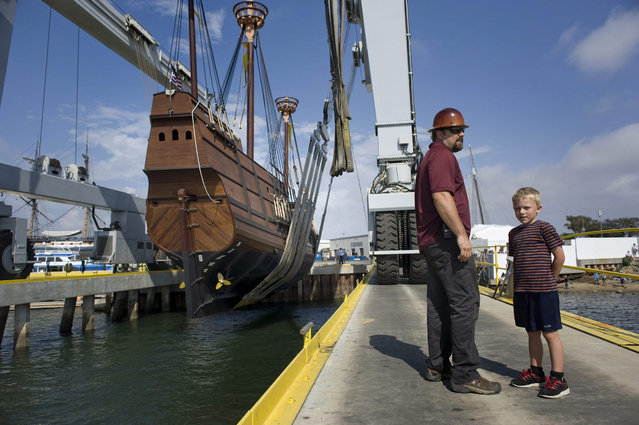 A dock worker and his son walk on the pier next to the ship San Salvador, which is a working replica of the Spanish galleon by the same name, after it was lowered into the San Diego Bay in Chula Vista, California, USA, 29 July 2015. The original San Salvador voyage in 1542, led by Portuguese explorer Juan Rodriguez Cabrillo, was the first ship to sail into the bay. (Photo by David Maung/EPA)