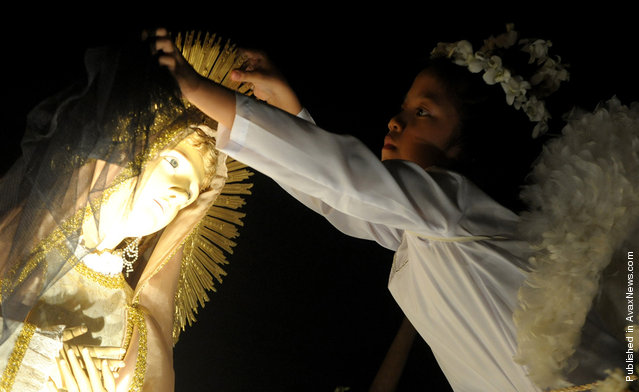 A child dressed as an angel lifts the veil over a statue of Mother Mary during an Easter mass outside St. Domingo Church in Quezon City, east of Manila, Philippines, on April 24, 2011. The traditional Salubong mass reenacts the meeting of the Risen Christ and the sorrowful Mother Mary on the dawn of Easter Sunday